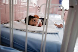 A physically and mentally disabled child lies in a hospital bed.