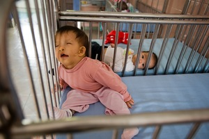 Infants born with deformities rest in their cribs.