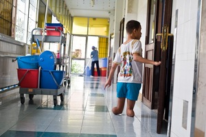 A boy born with deformities in the limbs walks back to his room after helping staff clean up after lunch.