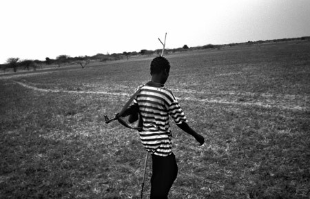 A 15 year old Nuer tribesman, carries his AK-47 as he walks in the Upper Nile region of South Sudan. Most men and boys in the area carry arms. © Tomas van Houtryve