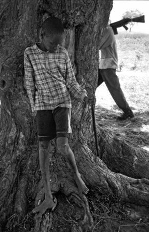 A young Nuer boy rests in the shade of a tree while a tribesman carrying an AK-47 walks past. © Tomas van Houtryve