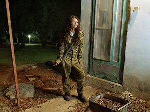 "Dana, a sniper instructor, outside her room, Kibbutz Kfar Hanassi, Israel, 2005. From the series ""Serial No. 3817131"" © Rachel Papo"