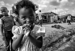 © Tony Corocher - Contrasts: Curiosity & diffidence, desperation & indifference.Through the streets of Mathare Slum (Nairobi). The contrast between the innocent beauty of the young girl, the vivid diffidence of the boy behind her, the finality of the desperation shown by the man on the ground behind her and the indifference of the people passing by… this is the ensemble of feelings that runs throu