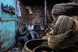 © Tony Corocher - The production process.Inside Makadare, one of the largest markets/slums. People are working on the production of shoes from old tires. There is the raw material, the manufacturing and the final product.