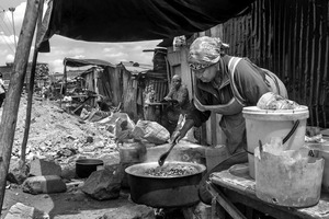 © Tony Corocher - High quality, protein soup ready... On the street of Mathare Slum, Nairobi. This woman is preparing a basic meal which will be sold to the people walking by... most people (especially women) always find something to do to make a living. There are many women like this one, cooking or doing some other kind of activity on the streets of Mathare, kibera and in all the other slums.