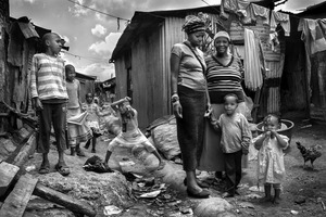 """© Tony Corocher - A happy family... (Mathare - Nairobi). This family is made up of 3 women (mother and 2 sisters)… the father disappeared a long time ago. These women take care not only of their own children (which are a few as you can see) but have also started a project to try to rescue the so called """"Street Children"""" (see next photo). These children sniff glue, oil and solvents and eat from the"""