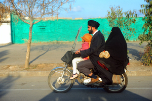 An Iranian Shiite Mullah rides his motorbike with his wife and child in the holy city of Qom, situated 120 km to the south of Tehran.  Qom, IRAN - December 2008 © Copyright 1979-2009 Alfred Yaghobzadeh. All rights reserved.