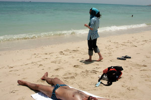 A Kish Island beach. While men are allowed to strip down to the tiniest of swim suits, Iranian women are obliged to  wear full Islamic dress even when going for a swim. Kish Island, IRAN - May 2006 © Copyright 1979-2009 Alfred Yaghobzadeh. All rights reserved.