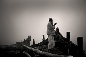 Aged 65, Aiyub Ali rises early to offer his prayers before a full day loading the boat with golpata. Sunderban, Satkhira. © Munem Wasif