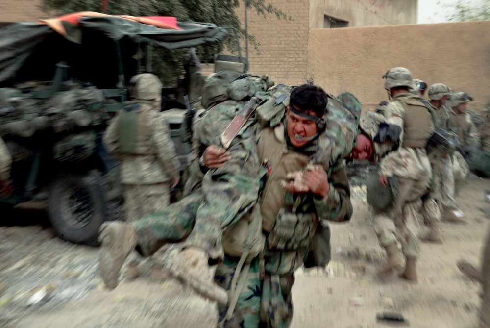 """Diwaniya April 7, 2003. US Marines remove their dead and wounded after an artillery shell scored a direct hit on a US armored vehicle during an attack on Diwaniya Bridge. From the book """"Photojournalists on War"""" © Gary Knight/VII"""