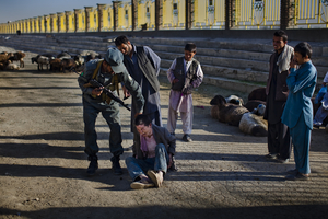 A policeman threatens a homeless child, who was sleeping on these steps, near the stadium in Kabul. © Michael Christopher Brown