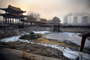 The Shuogang group steel factory on the outskirts of Beijing. Despite the government promising to close many major polluting factories within city limits following the 2008 Olympics several are still operating behind closed doors. At dawn every day the factory waste-water pipe illegally spews hazardous chemicals into a local lake. ©Souvid Datta, RPS/Photographic Angle, IdeasTap/Magnum Photos
