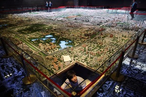 A worker peers out from beneath the miniature scale model of Beijing's vast central districts, while developers have a discussion above. Beijing's population has risen from 11 million to over 20 million since 2000. As the world's second most populated country with ferocious economic ambition and growth, the effective, sustainable planning of urban development lies at the heart of China's future.