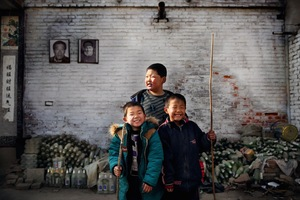 Jaw-long (centre) stands with his friends in front of his house in Nuguang village on the outskirts of Xingtai. The portraits behind depict his father and uncle who both worked in the nearby steel factory and died due to undiagnosed respiratory problems. Jaw-long has dropped out of school to help his mother with her glass recycling business.  ©Souvid Datta