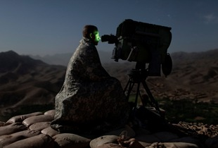 A U.S. Army soldier from the 10th Mountain Division surveys a road with a Long Range Acquisition Sight, on an observation post in the Tangi Valley, Wardak Province, Afghanistan, on September 4, 2009. © Adam Ferguson