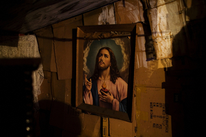 "A portrait of Jesus hangs in a cardboard home in the Stara Gazela settlement in ""old"" Belgrade. © Matt Lutton"