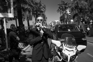 "a security agent liaises with a collegue using his wrist radio while the stars of ""The Expendables 3"" greet the crowds on the Croisette, 2014  © Alison McCauley"