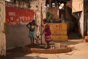 Mangueira is another favela, just a stone's throw away from the world famous Maracana stadium. Many of the favela's residents are forced to do their laundry in the street, as their homes do not have running water. © Manu Valcarce