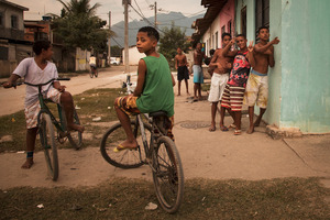 """The symbol """"CV"""" (visible in the back, in the group of 3 boys), stands for """"Comando Vermelho,"""" one of the three main drug cartels in Brazil. Within this favela, the undereducated children are easy targets for gang recruiters.© Manu Valcarce"""