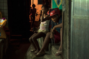 Some residents report that delinquency has actually increased since the police came. With the drug gangs gone, the neighborhoods face a power vacuum and petty crime has become even more rampant. Still, these children listen to music on the steps of a grocery store in Rochina. © Manu Valcarce