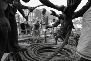Workers uncoiling a thick steel-made cable (used to tie ship parts together). © Pierre Torset