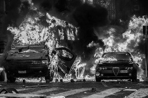A car and a police truck are set on fire  by the rioters  after the Senate and Lower House vote of confidence that resulted in a razor-thin victory for Berlusconi to continue his mandate.  14 December 2010. © Riccardo Budini / UnFrame