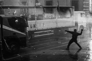 A hooded rioter hurls a cobblestone against a water cannon police truck in  San Giovanni square during the long and devastating clashes triggered by organized violent fringes of protesters.  15/10/2011. © Riccardo Budini / UnFrame