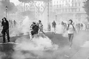 Dense white clouds of tear gas are released by the canisters fired during the clashes triggered by organized violent fringes of protesters.  15 October 2011. © Riccardo Budini / UnFrame