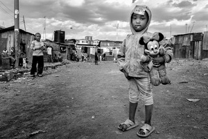 © Tony Corocher - Western beauty in Nairobi's hell (Kibera Slum - Nairobi) - This little girls caught my eye because of a really strong contrast … she was holding a classic symbol of western beauty inside one of the harshest realities in the world.