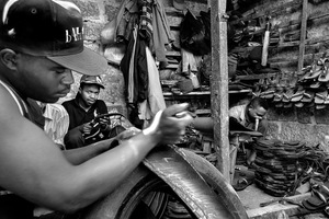 © Tony Corocher - The Production Process (Makadare Market/Slum) - Here we are inside Makadare, one of the largest markets/slums in Nairobi, where people work with old tires and rubber to produce shoes, tools and various other objects.