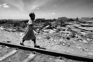 © Tony Corocher - Africa, where are you going? - A young girl playing on the railway that runs through Kibera (the second largest slum in the world). All you can see in the background is Kibera with over one million people… while I was taking this picture my mind kept thinking about what kind of future awaits the African countries.