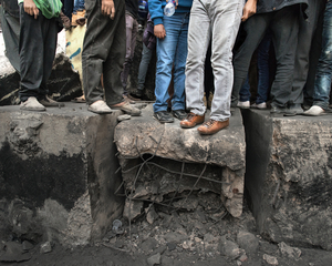 Protesters stand on rubble from the wall. © Domenico D'Alessandro