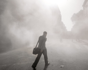 A man goes to work along a road infused by tear gas during the last days of clashes after Port Said verdicts.   © Domenico D'Alessandro