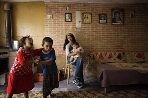 "© Julie Denesha (United States) ""Outcasts of Slovakia"": Simonka Mirgova and Patko Polhous sing and dance as Sonja Polhousova cares for her nephew Adrian Pista in the home she shares with her parents and siblings. Honorable Mention, LensCulture Exposure Awards 2009"
