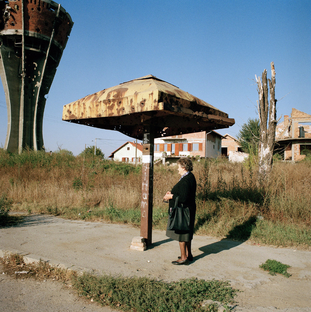 A lady waits for a bus in a residential area that was largely destroyed during the war. The damaged water tower on the left has become something of an icon for the town. © Colin Dutton