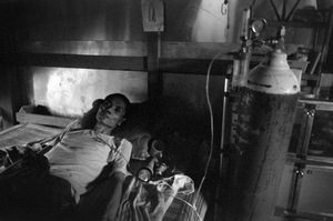"Sintku Township, Mandalay Division, Myanmar, 2013. Kwin Tone Sel, 42, lies in his home on the edge of the mining village. He contracted ""gun disease"" years ago, and has been deteriorating since. Apart from his oxygen tank, he receives no other medical attention. © Spike Johnson"