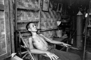 "Sintku Township, Mandalay Division, Myanmar, 2013. Kyi Tout Pout, 37. A miner with recently contracted ""gun disease"" rests in his house. ""I worry for my health, and for my sons, when I can no longer look after them,"" he says. © Spike Johnson"