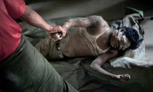 Sittwe, Myanmar, 2012. Maung Maung Chay's uncles identify his body at Sittwe's morgue. He was shot by the Burmese military, when he was found near a Rohingya village after curfew. The military shoot on sight, as a deterrent to both Rakhine and Rohingya arsonists. © Spike Johnson