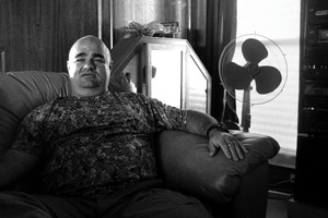 Dallas, Texas, 2010. Ralph Severe, Texas Survivalist instructor, in the front room of his home. © Spike Johnson