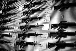 "Dallas, Texas, 2011. Assault rifles line the walls of ""Cheaper Than Dirt Guns,"" a popular spot for The Texas Survivalists. © Spike Johnson"