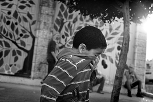 A child no more than 7 or 8 fights his way through tear gas fogging the streets. © Will Hilton