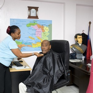Julio Jean Pierre is a host on Télévision Nationale d'Haïti (TNH). He's being made up a few minutes before going on air. Behind him, a bust of Alexandre Pétion, president of the Haitian Republic from 1806 until his death in 1818, one of the fathers of the nation. Port-au-Prince. Haiti. 2012. © Paolo Woods/INSTITUTE