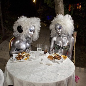 "At the Hôtel Karibe, above Port-au-Prince, two go-go girls dig into fried chicken after dancing for hours at the concert of a local singer, J Perry. Juvénat, Pétion-Ville. Haiti. From the series, ""STATE"" © Paolo Woods/INSTITUTE"