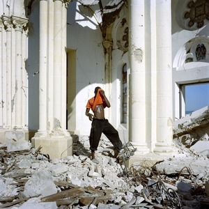 "In Port-au-Prince's Notre Dame Cathedral, a man looks for iron to recycle from the ruins of the earthquake. Port-au-Prince. Haiti. From the series, ""STATE"" © Paolo Woods/INSTITUTE"
