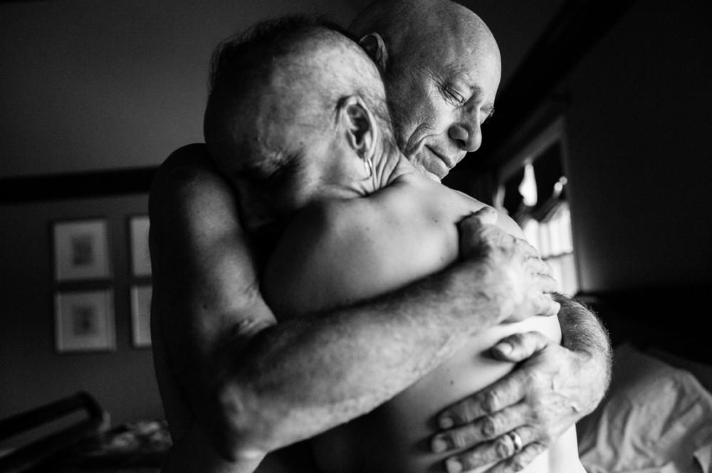 Howie and Laurel Borowick embrace in the bedroom of their home. In their thirty-four year marriage, they never could have imagined being diagnosed with stage-4 cancer at the same time. Chappaqua, New York. March 2013 © Nancy Borowick