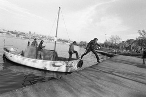 A man jumps from a small fishing boat onto the shore of Golden Horn.