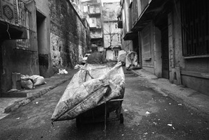 A man pulls cart holding a big sack for collecting cardboard and plastic for recycling.