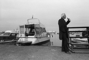 A man, standing beside boats moored on the Golden Horn shore, takes a drink from a bottle of Efes beer.