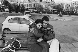 A couple, sitting on a bench, cuddle each other.