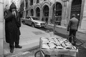 A banana vendor eats one of his bananas as he waits to make a sale.